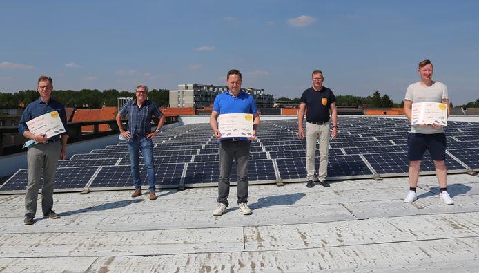 De winnaars van de zonnepanelenwedstrijd zijn bekend. V.l.n.r: Frank Witlox (winnaar), Walter Brat (duurzaamheidsschepen), Bart Hicguet (winnaar), Paul De Swaef (schepen Ruimtelijke Ordening) en Dave Soetewey (winnaar) op het dak van Sporthal Vordensteyn met haar fotovoltaïsche zonnepanelen