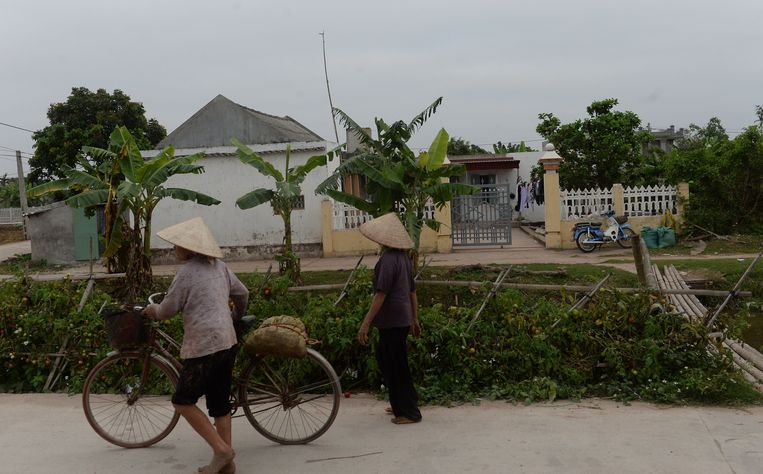 Villagers walk past the native home of Doan Thi Huong, a suspect involved in the assassination of Kim Jong-Un's half-brother, in Nghia Hung district, northern province of Nam Dinh on February 22, 2017. Detectives probing the assassination of Kim Jong-Un's half-brother want to question a North Korean diplomat, Malaysia's top policeman said. Royal Malaysian Police chief Khalid Abu Bakar said Vietnamese suspect Doan Thi Huong, 28, and Indonesian Siti Aishah, 25, had been trained to swab the man's face, practising in Kuala Lumpur before the assault at the airport.  / AFP PHOTO / HOANG DINH NAM Beeld AFP