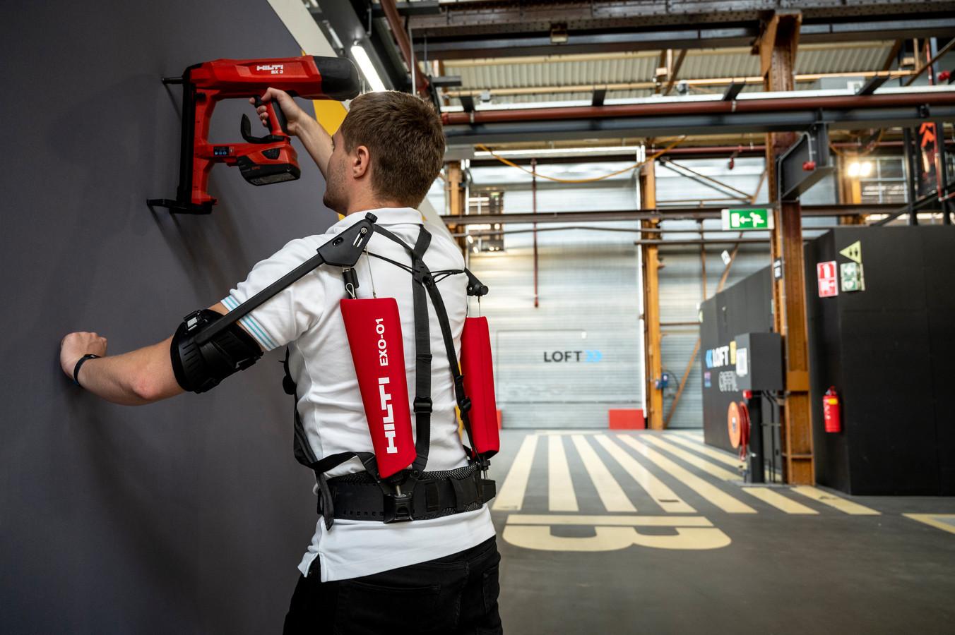 Het exoskelet dat de armen ondersteund helpt bijvoorbeeld bij het boren van gaten in de muur.