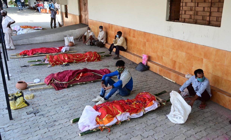 Familieleden wachten bij de lichamen van hun geliefden op de crematie in Uttar Pradesh, India. Beeld Photo News
