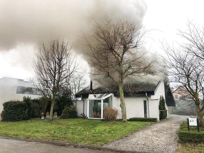 Toen de brandweer arriveerde kwamen vlammen en dikke rook reeds door het dak van de woning.