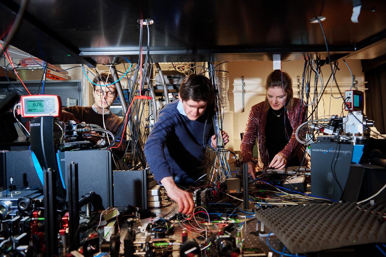 Fysici Matteo Pompili, Hans Beukers en Sophie Hermans sleutelen in de kelder van quantuminstituut QuTech aan de TU Delft aan de  opstelling, vol laserbundels, kabels, lenzen, spiegels en meetapparatuur. Beeld Niels Stomps
