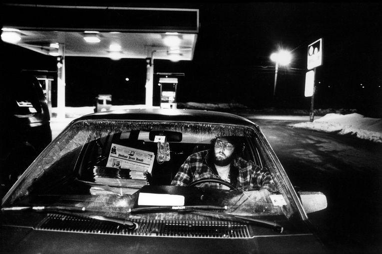 Bij het tankstation van Kingfield, Maine, drinkt een krantenbezorger voor dag en dauw een kop koffie, 2001.  Beeld Tim Dirven