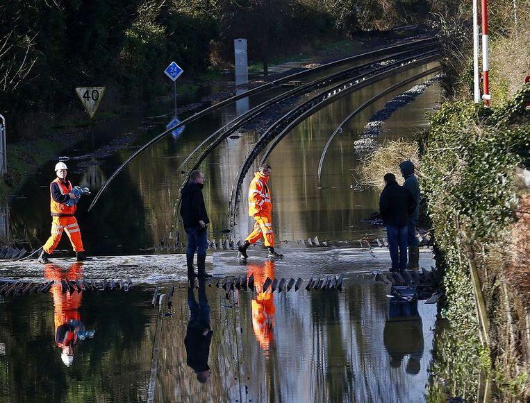 Spoorwerkers in Datchet.<br /><br />De Engelse overheid waarschuwt voor ernstig overstromingsgevaar in 14 plaatsen langs de de rivier de Theems. Duizenden huishoudens moeten zich daar op voorbereiden. Sinds december zijn al zo'n 8000 woningen getroffen door het hoge water.<br /><br />Ondanks alle maatregelen is vanmiddag het dorp Datchet ook ondergelopen.<br /><br />Na twee maanden van recordneerslag voorspellen meteorologen nog zeker tot en met donderdag iedere dag regen. Vooral de graafschappen Berkshire en Surrey zullen vermoedelijk met wateroverlast te maken krijgen. <br /><br />De Britten worstelen met het natste weer sinds 1766. Het water in de rivier stond in tientallen jaren niet zo hoog en stijgt nog steeds. Beeld reuters