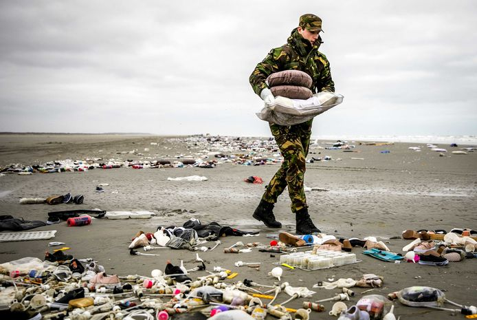 Militairen ruimen de spullen op die op het strand zijn aangespoeld