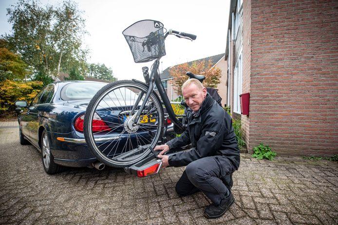 Jan bij zijn Jaguar waarmee hij fietsen ophaalt en brengt. Benzine is zo duur geworden dat hij voor de service moet laten betalen.