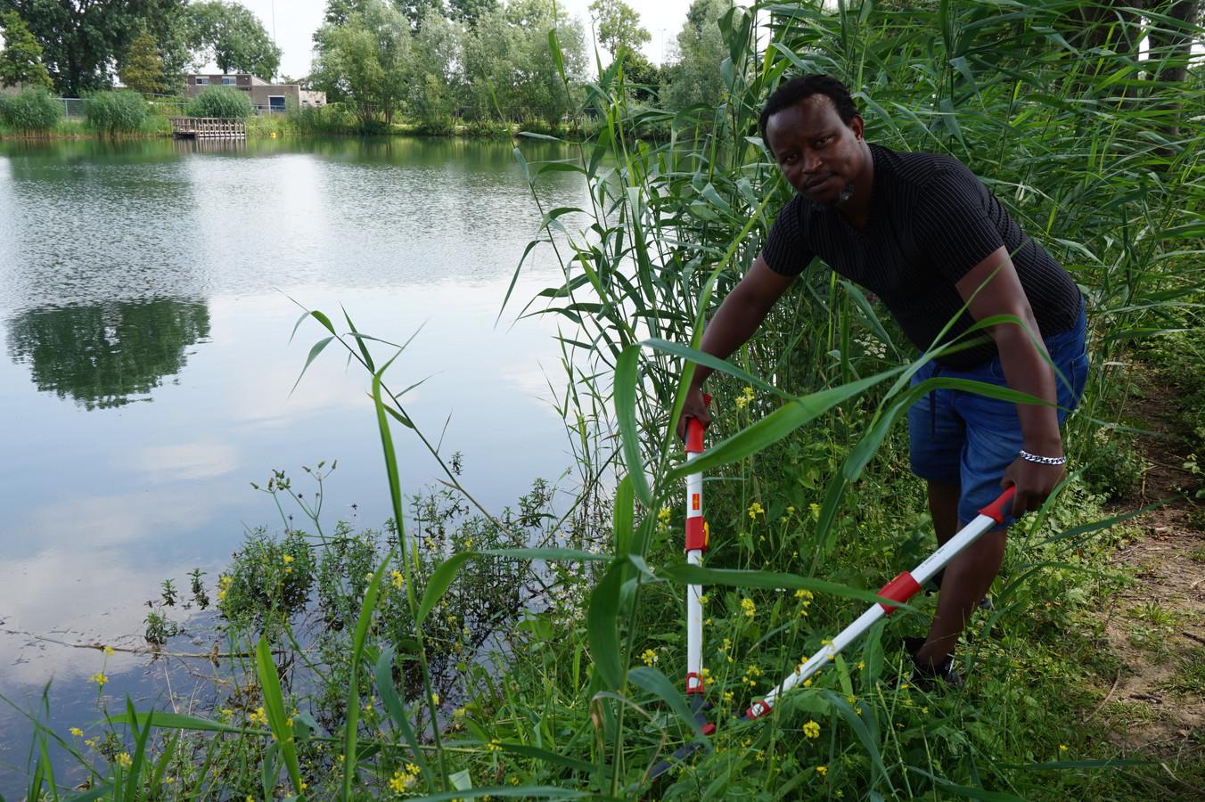 Pascal gaat op sportpark De Pas in Elst het onkruid op de oevers te lijf.