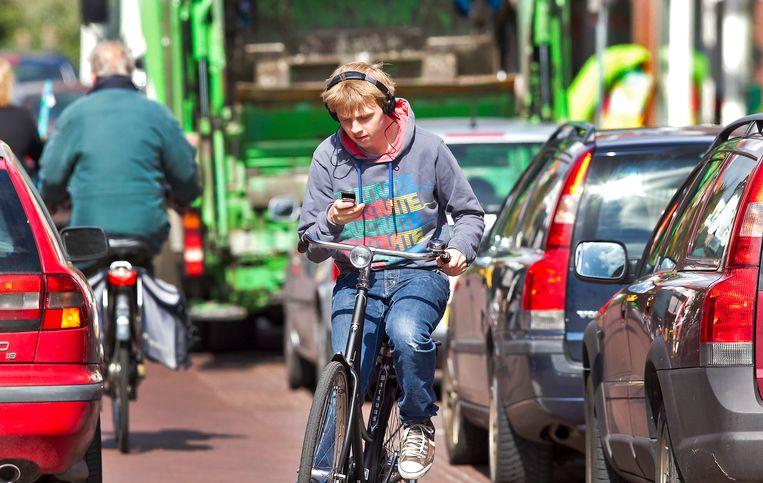 Telefoneren en muziek beluisteren tijdens het fietsen vergroten de kans op een ongeval. Beeld ANP