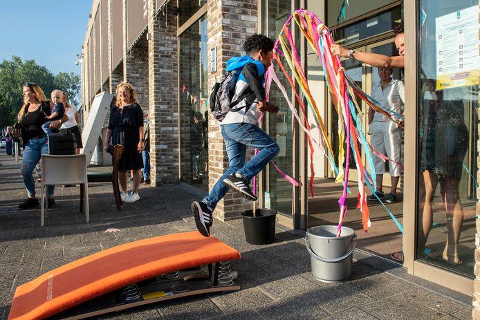 Basisschool Het Noorderlicht opent het nieuwe schooljaar: de kinderen springen via een springplank de school in.