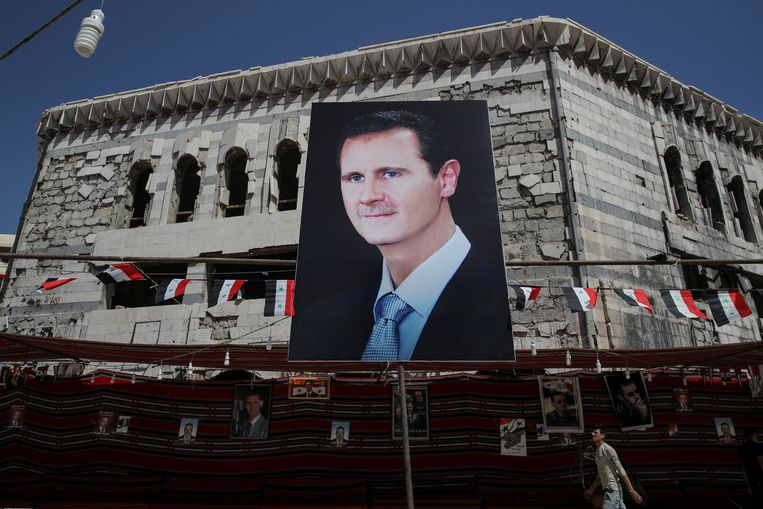 Een affiche met Assad op in Damascus.  Beeld REUTERS