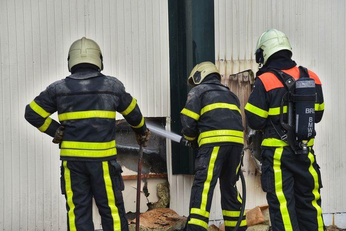 De brandweer zaagt een gat in de zijkant van het frietkot, om beter bij het vuur te kunnen.