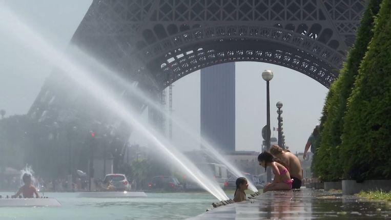 Mensen zoeken verkoeling in de fonteinen aan Trocadero, bij de Eiffeltoren
