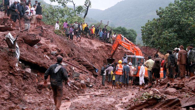Reddingswerkers op de plek van de aardverschuiving in Malin. Beeld AP