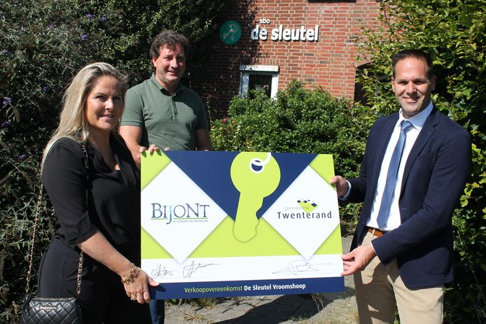 Darinka Dieperink en Ard Pierik van Bijont (l) sluiten officieel de deal met wethouder Bart-Jan Harmsen over het oude schoolgebouw De Sleutel (op de achtergrond).