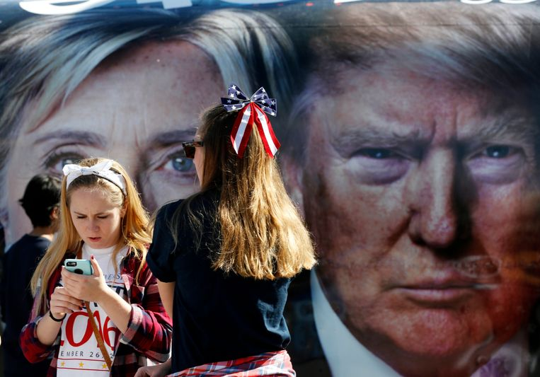 Amerikanen bekijken een affiche die het eerste debat tussen Hillary Clinton en Donald Trump aankondigt. Beeld AP