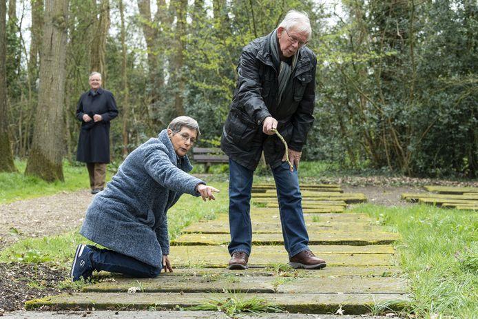 Voorzitter Tineke van Buren van de Stichting Noabers van 'n Oalen Griezen en preses Paul Janse van Stichting 't Oale Karkhof wijzen de grafstenen aan die worden gerestaureerd.