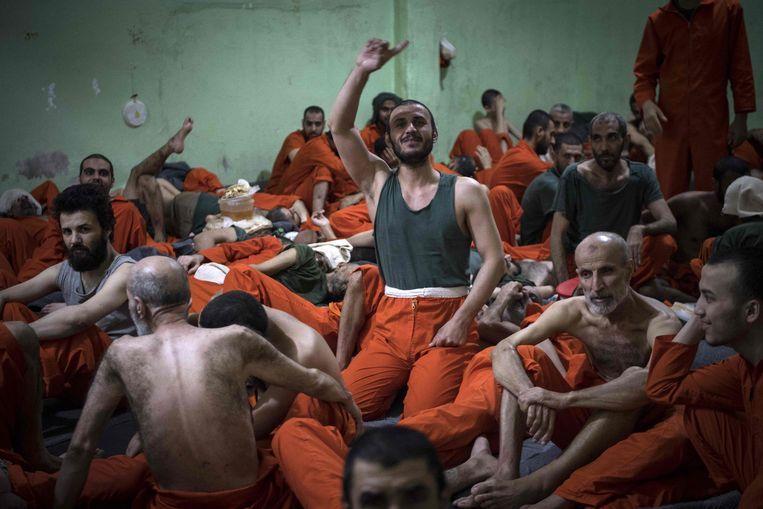 Mannen die verdacht worden van lidmaatschap in een gevangenis in Hasakeh in het Noordoosten van Syrië.  Beeld AFP