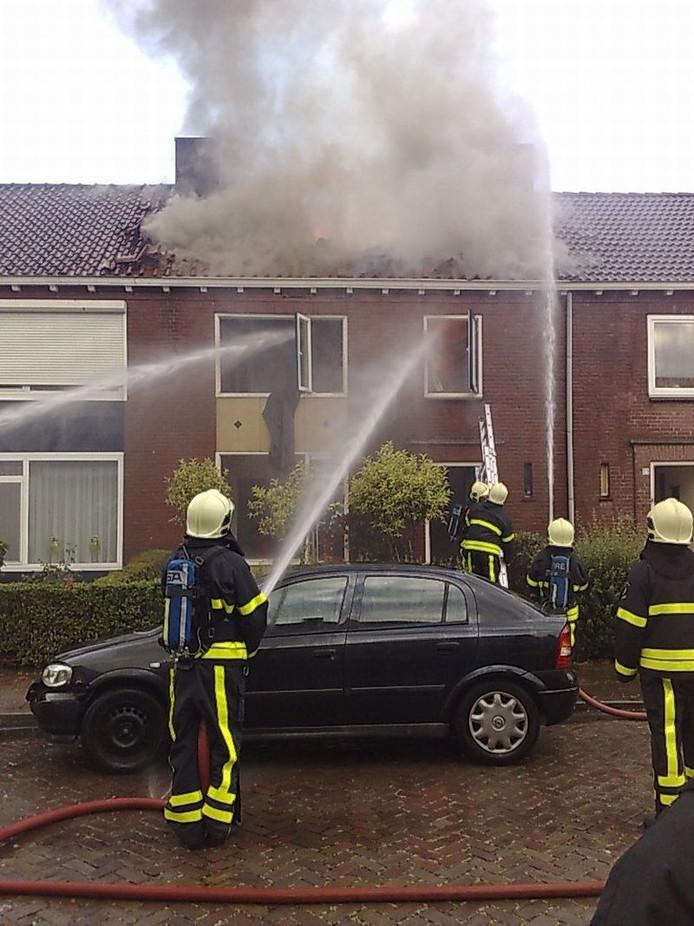 De brandweer bestrijdt de brand in de woning in Veldhoven. foto Bert Jansen