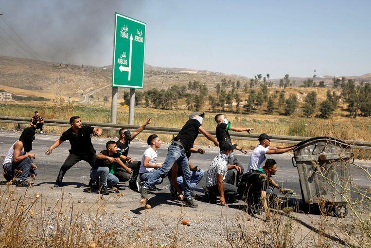 Palestijnse demonstranten gooien stenen naar Israëlische soldaten nabij Nablus.  Beeld Reuters