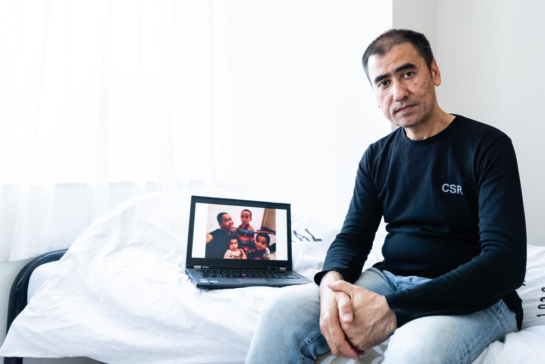 De Oeigoerse vluchteling Ablimit Tursun zit op bed in zijn studio in Gent, op zijn laptop een foto van zijn vrouw en kinderen.