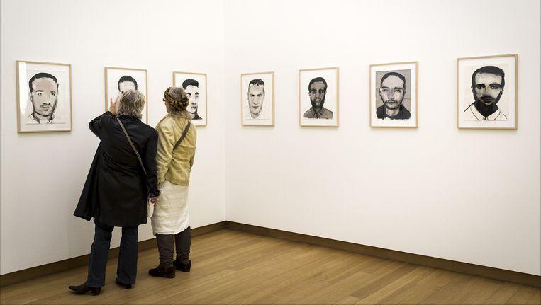 Twee vrouwen beoordelen het werk YOUNG MEN van Marlene Dumas in het Stedelijk Museum. Beeld anp