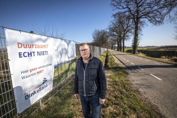 Fons Maathuis bij een van de grote banners die hij heeft laten maken tegen grote windmolens.