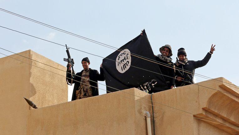 Iraakse soldaten tonen de vlag van IS nadat ze een bastion van de terreurgroep in Mosoel hebben veroverd. Beeld EPA