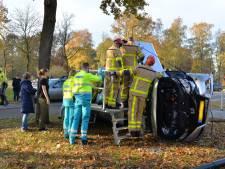 Auto belandt op z'n kant na botsing in Apeldoorn: brandweer bevrijdt vrouw