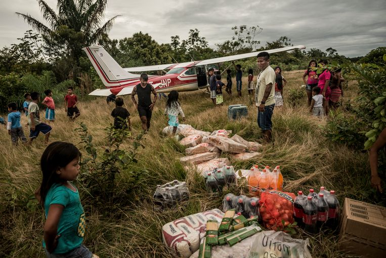 Leden van de Munduruku-stam laden voedsel en drank uit. Dat hebben ze als een soort vredeoffer gekregen van de mijnwerkers die hun land komen inpalmen.  Beeld NYT