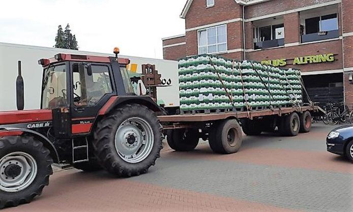 De tractor met volgeladen platte wagen voor de supermarkt in Gramsbergen.