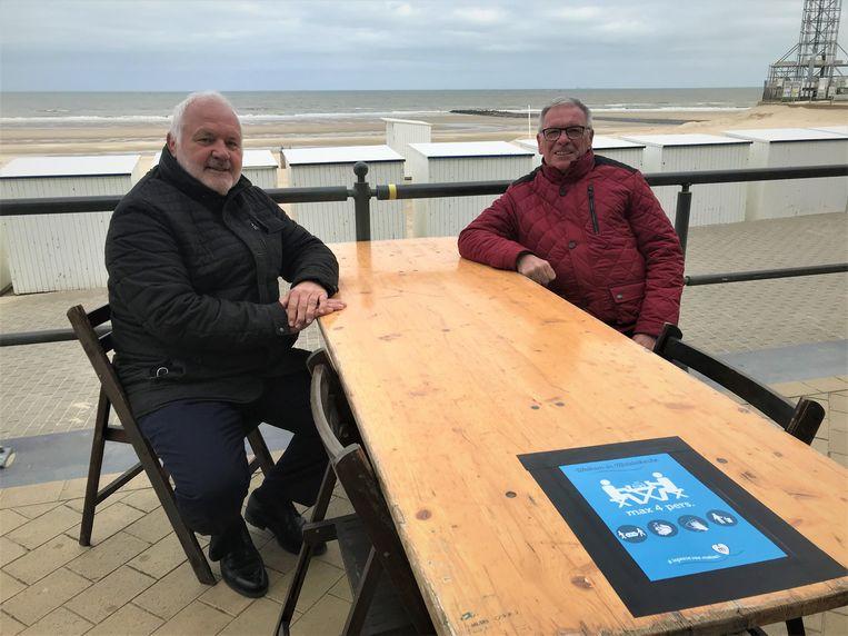 Burgemeester Dedecker en schepen De Poortere nemen plaats aan een tafeltje op de zeedijk. Beeld Benny Proot