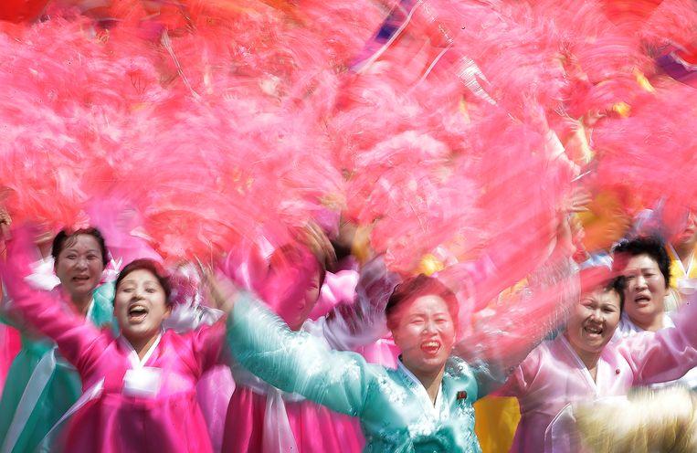 Vrouwen in kleurige gewaden zwaaien tijdens de parade. Beeld AP