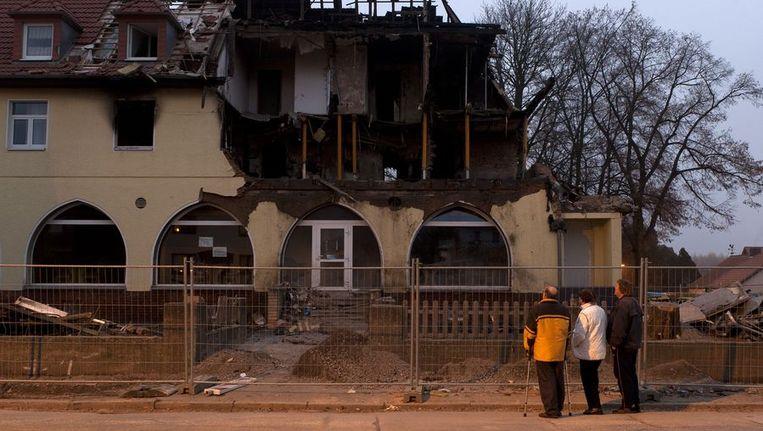 Mensen kijken naar een uitgebrand huis, dat vermoedelijk door een lid van het nazi-netwerk in brand is gezet. Beeld afp