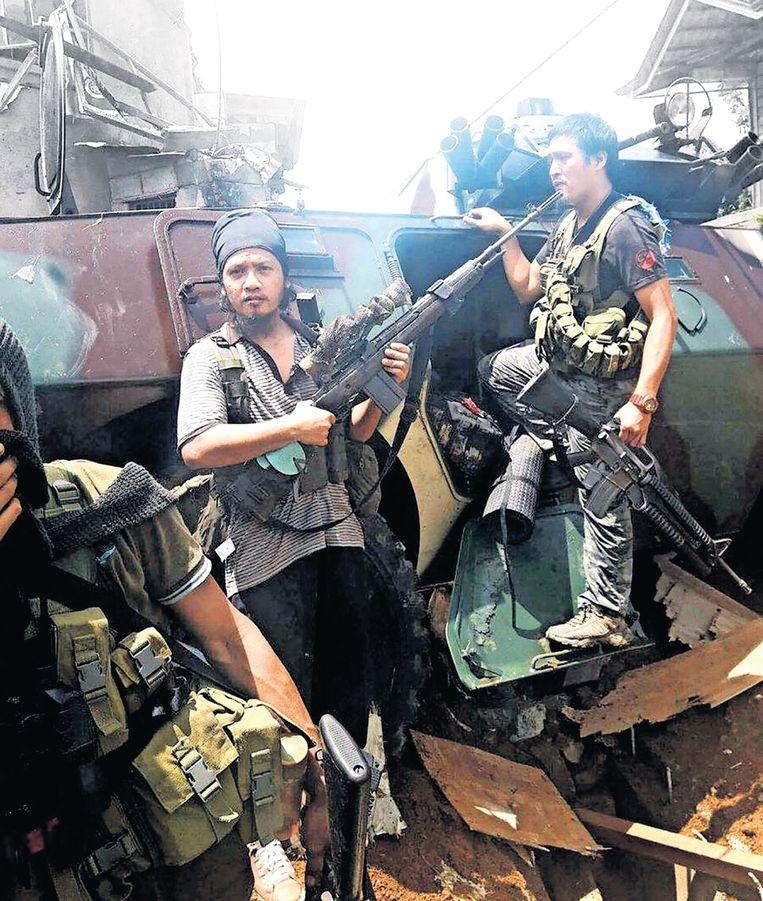 Dit zouden IS-strijders zijn, bij een pantservoertuig van het Filippijnse leger. IS-fans postten deze foto op Telegram. Beeld rv