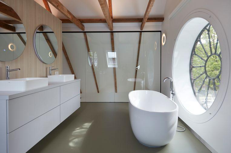 De badkamer met vrijstaand bad en roosvenster. Beeld Herman van Heusden