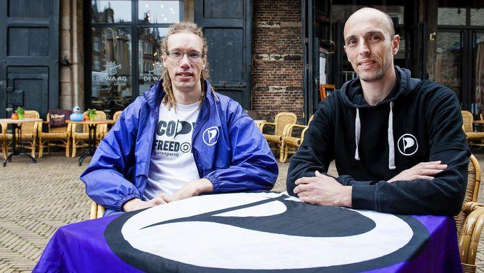Geert-Jan Meewisse (links) en Michiel van den Boogaard tonen de vlag van de Piratenpartij bij De Waag.