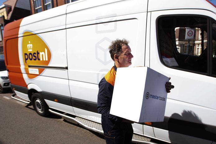 Een pakketbezorger doet een contactloze bezorging. Bij PostNL is het deze dagen aanzienlijk drukker dan voor de coronacrisis.
