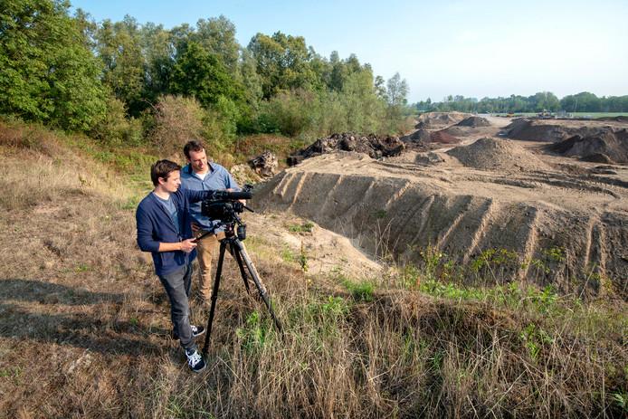 Pieter van den Berg (voor) en Bram Hanstede op het gebied tussen de op- en de afrit van de snelweg waar hun Zonpark A348 moet komen. Ze maken er ook een film van.