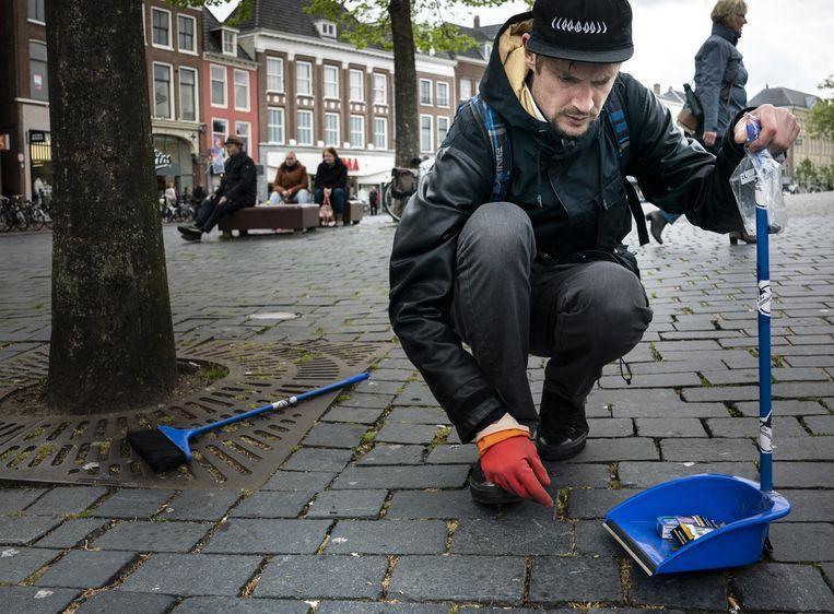 Alain Muller raapt sigarettenpeuken in Leeuwarden. Beeld Reyer Boxem