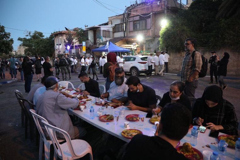 Palestijnse families die mogelijk uit huis gezet worden zitten aan een iftarmaal in hun straat, terwijl Israëlische politie en kolonisten toekijken.  Beeld EPA