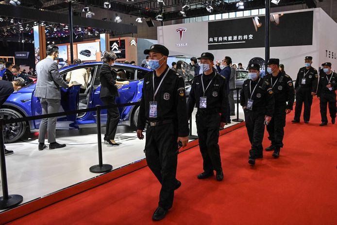 Beveiligers bij de stand van Tesla in Sjanghai, waar een vrouw op een tentoongestelde Model 3 kroop om luidkeels haar ongenoegen over haar auto te uiten.