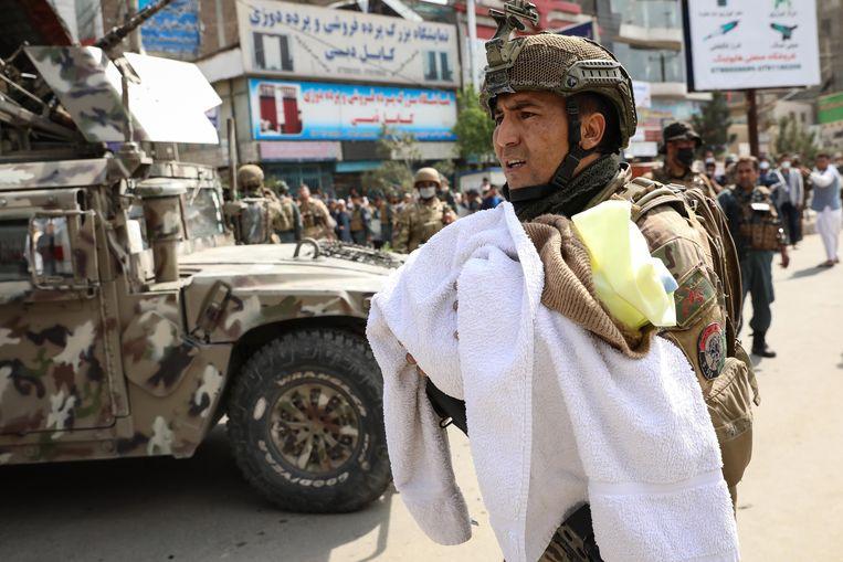 Een Afghaanse soldaat brengt een baby'tje in veiligheid na de aanslag op het ziekenhuis.  Beeld EPA