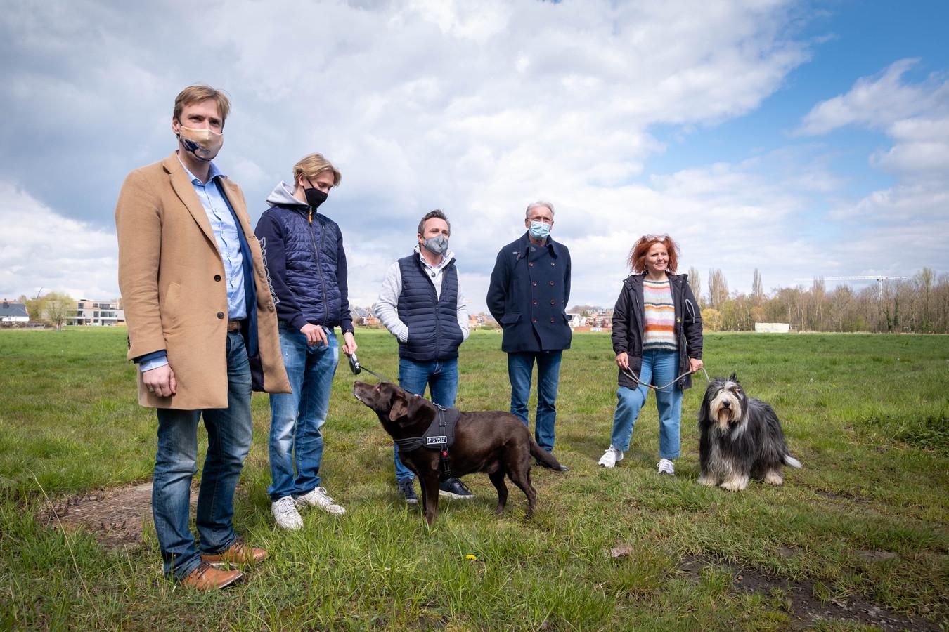 Schepenen Bert Wollants, Thierry Suetens en Rik Pets met twee hondenbaasjes op de plaats waar de stad Lier een tweede hondenspeelzone wil creëren.