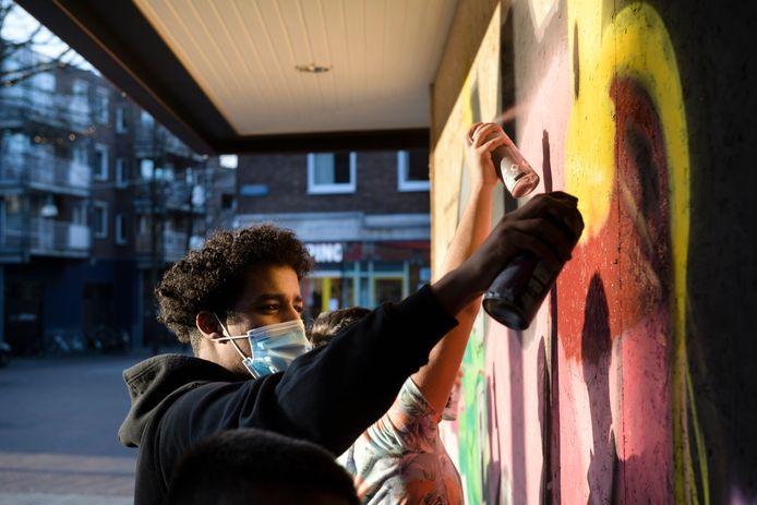 Jongeren bespuiten de betimmeringen van House of Snobs, in het kader van het graffitiproject van Alifa.