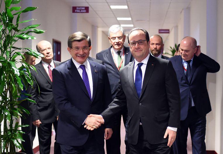 De Franse president Hollande schudt de hand van de Turkse premier Davutoglu tijdens de EU-Turkije-top in Brussel. Beeld ap