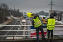 Gele Hesjes hangen een spandoek en een Nederlandse vlag aan een viaduct over de A1, om zo aandacht te krijgen