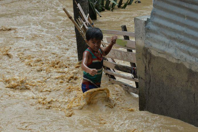 Een kind waadt door het water in Santa Rosa, ten noorden van Manila.