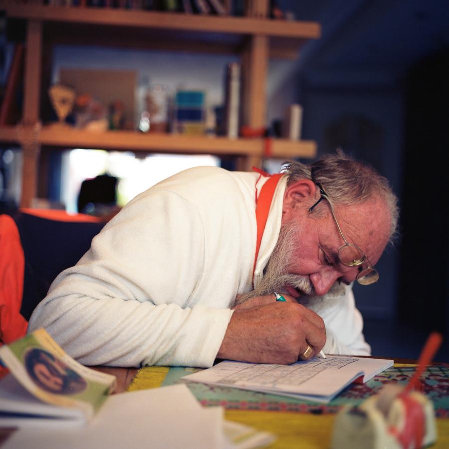Straatprediker Arnol Kox buigt zich geconcentreerd over een sudoku.