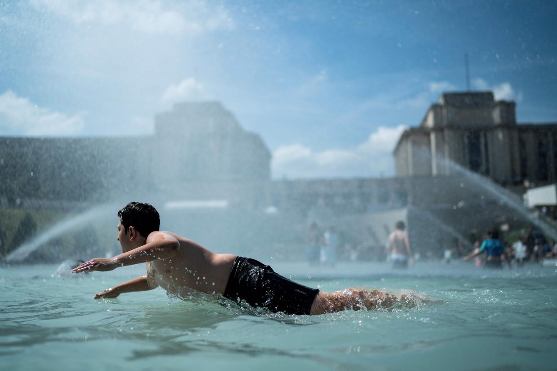 Een tiener zoekt verkoeling in de fontein van Trocadero in Parijs. Beeld AFP