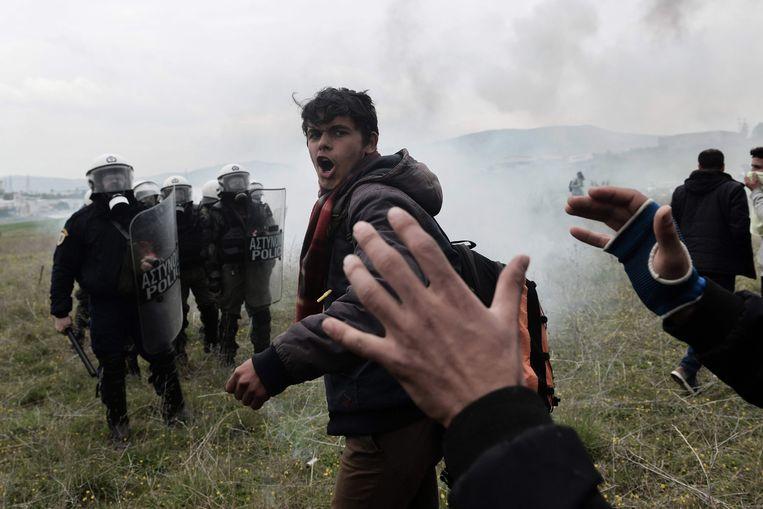 Migranten roepen leuzen tijdens schermutselingen met de Griekse oproerpolitie op 6 april bij een kamp in Diavata, een buitenwijk van Thessaloniki. De onrust hield dagenlang aan. Beeld AFP